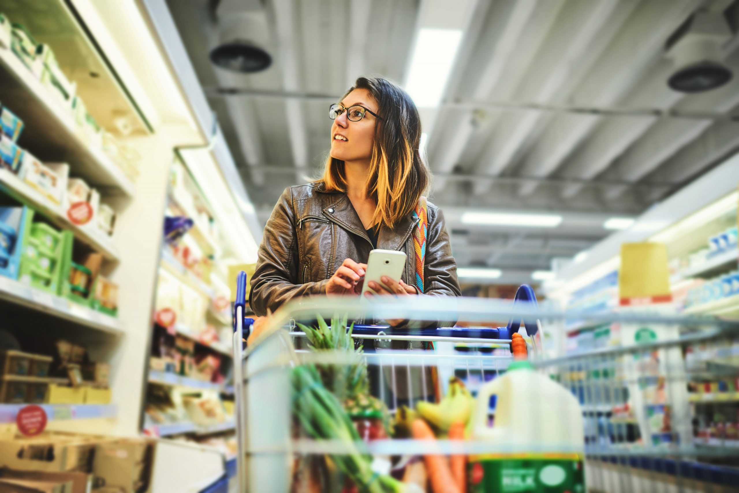 Lady in supermarket browsing products with mobile phone in hand